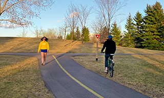 A pedestrian and a cyclist stay at least two metres apart while sharing a trail