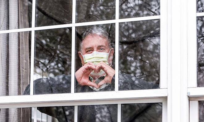 Middle age man behind a window, making a heart shape with his hands