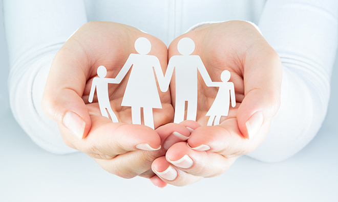 Hands carefully holding paper cut-out of a family