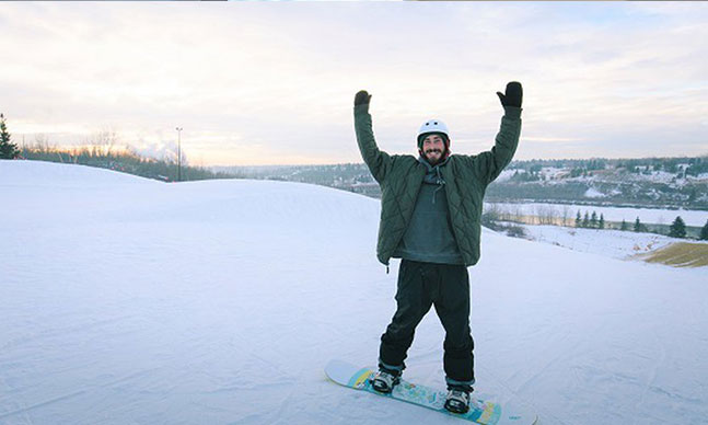 Snowboarder at top of hill, arms up and big smile