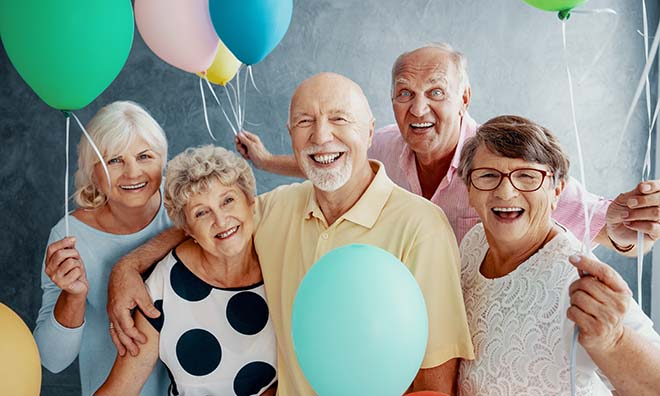Group of happy seniors holding ballons