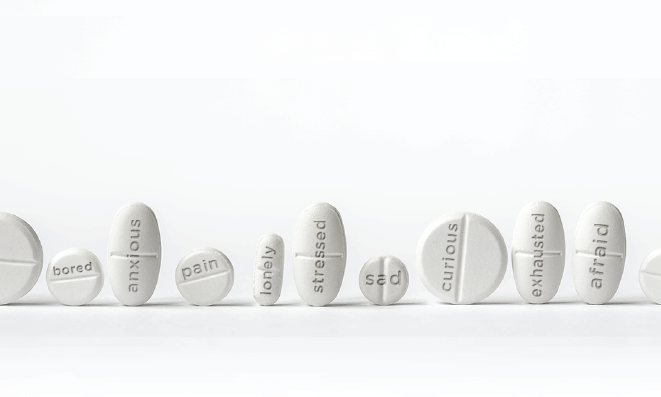 Image of medicine pills with words representing negative feelings printed on each of them -bored, anxious, pain, lonely.