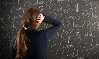Young girl looking at a chalkboard filled with questions - what, how, why, which...