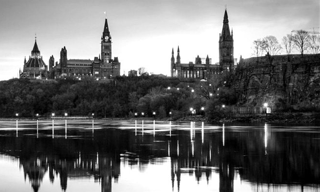 canadian legislative building overlooking a large body of water