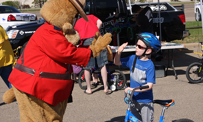 Safety bear giving a high-five to young kid wearing his helmet and holding his bike