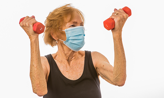 Female senior with disposable mask on her face holding two small weights in a bicep curl motion.