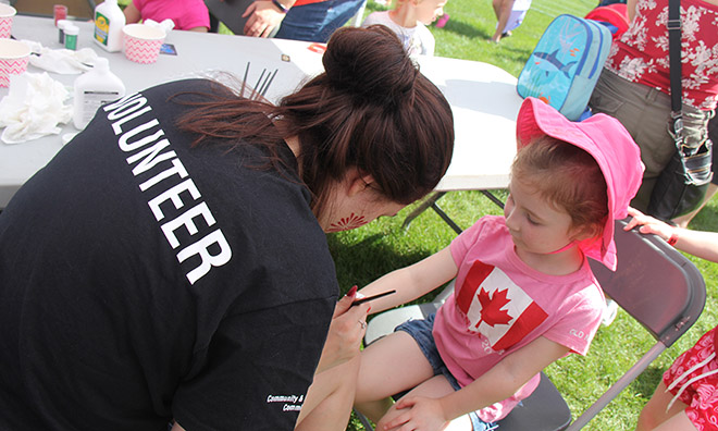 Volunteer with child at Canada Day celebration