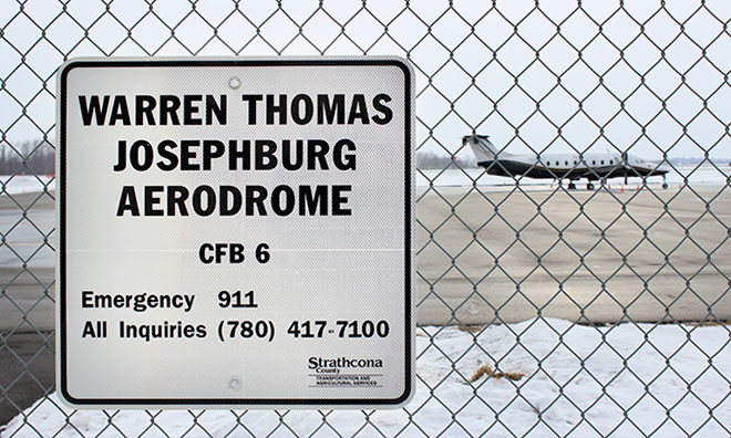 Image of sign on fence that says Josephburg Areodrome with a plane in the background