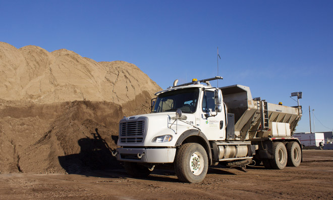 Sanding truck parked next to sand pile
