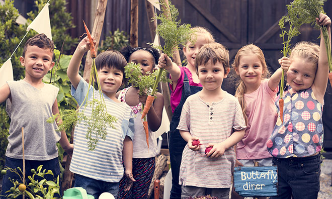 Image of school age children in a garden holding up vegetables
