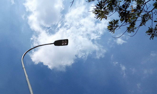 Street light against blue sky and clouds