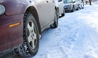 cars parked on the side of the road in winter
