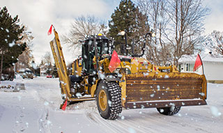 Grader clearing snow on a residential street.