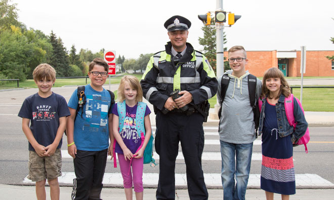Image of RCMP officer standing with school age children outside school