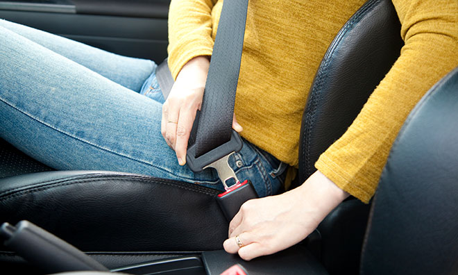 Image Of A Person Buckling Up Their Seat Belt