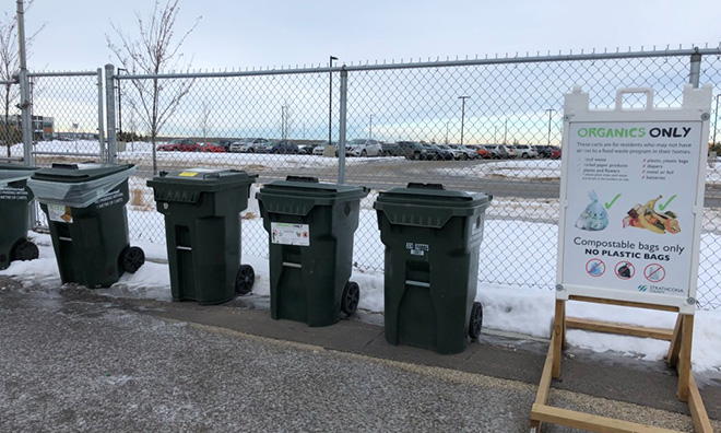 Image of green organics carts against a chainlink fence.