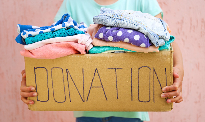 Woman holding a box of clothes with the word donation written on it.