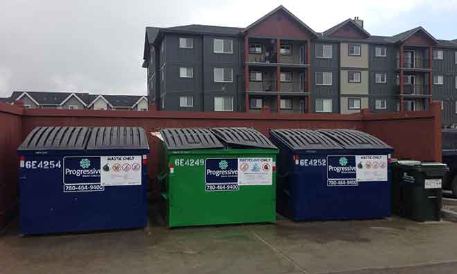 Waste and organics bins outside a multi-family building.