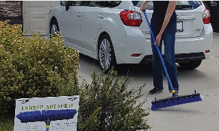 Image of a woman sweeping her driveway with a blue broom.