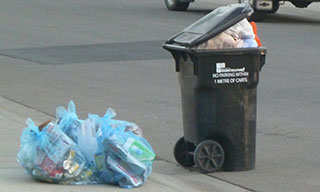 Image of waste cart full of garbage bags so that the lid cannot close.